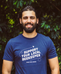 Man wearing navy blue t-shirt that says support your local beekeeper